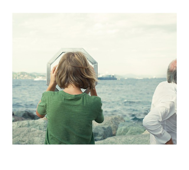 Boy, viewing scope, sea and cruise liner.