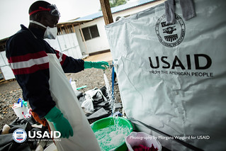 Staff at Island Clinic wash clothes of health workers after they have gone into the Ebola Treatment Unit | by USAID_IMAGES