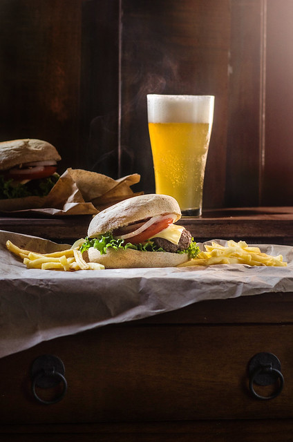 Burger with french fries and glass of beer on wooden table