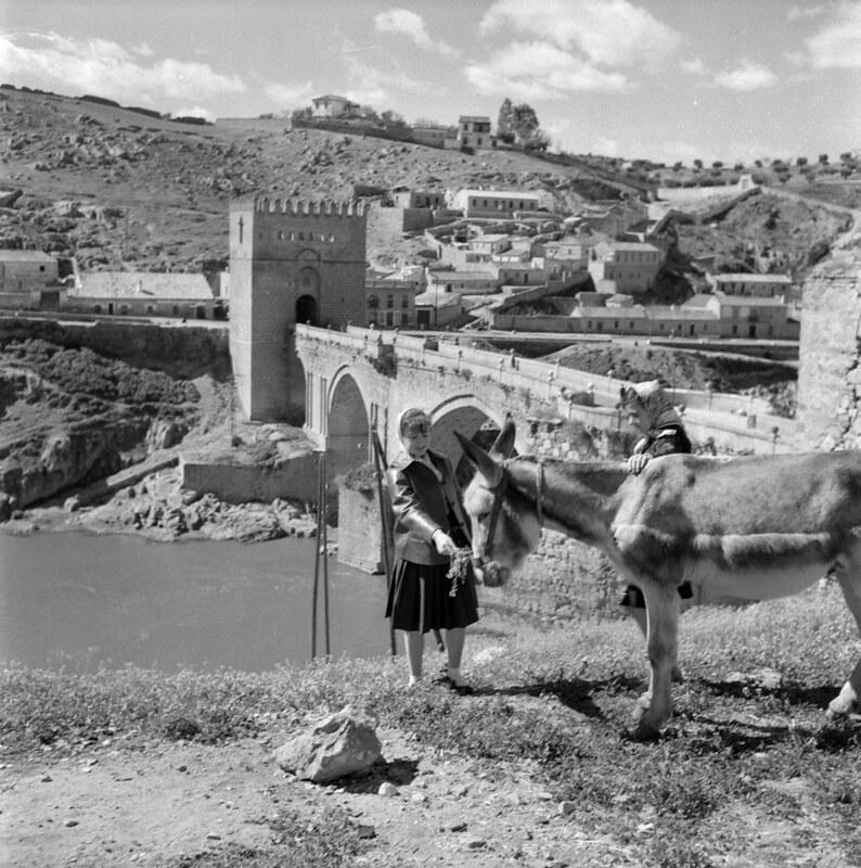 Dos mujeres y un burro en el Puente de San Martín en los años 50. Fotografía de Nicolás Muller  © Archivo Regional de la Comunidad de Madrid, fondo fotográfico