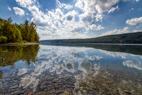 trees sky lake ny newyork reflection tourism nature water beautiful clouds forest landscape outside outdoors rocks hiking scenic hills adventure shore fingerlakes hemlock nys livingstoncounty dandangler