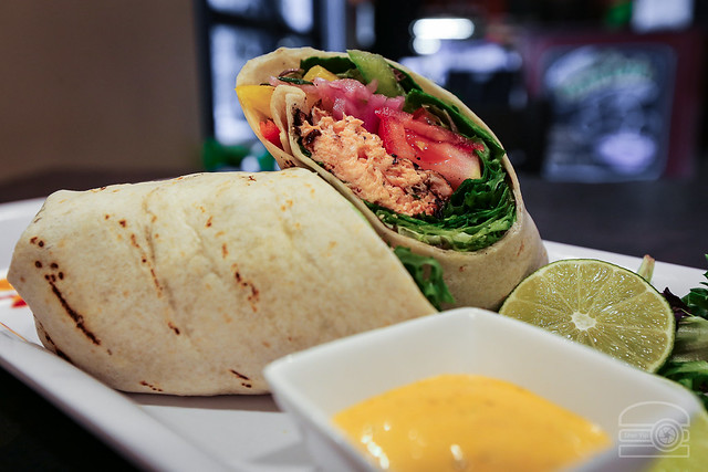 Jerk Salmon Wrap - Jerk Seared Salmon, Grilled Pineapple, Peppers, Onion, Tomatoes, Greens in a Grilled Wrap w/ Chili Garlic Mayo