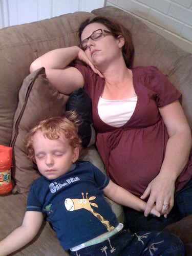 My son and pregnant wife asleep on the couch at 8pm.