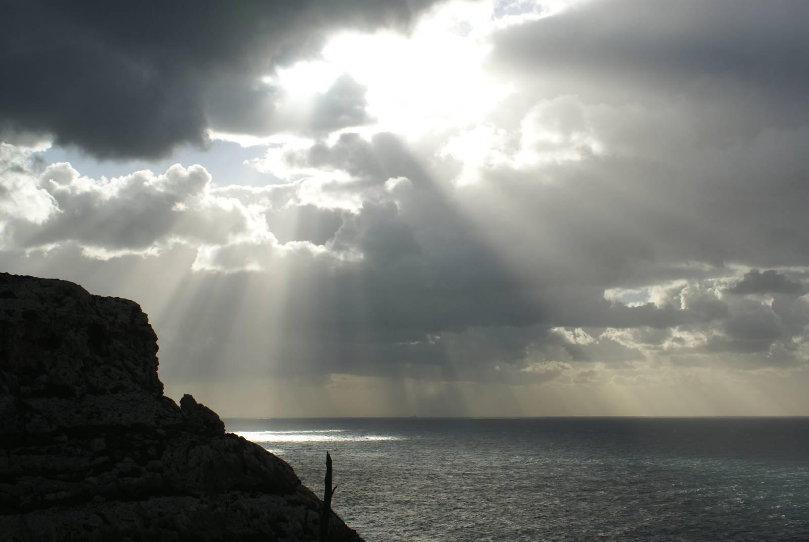 Sunlight shining through dark clouds