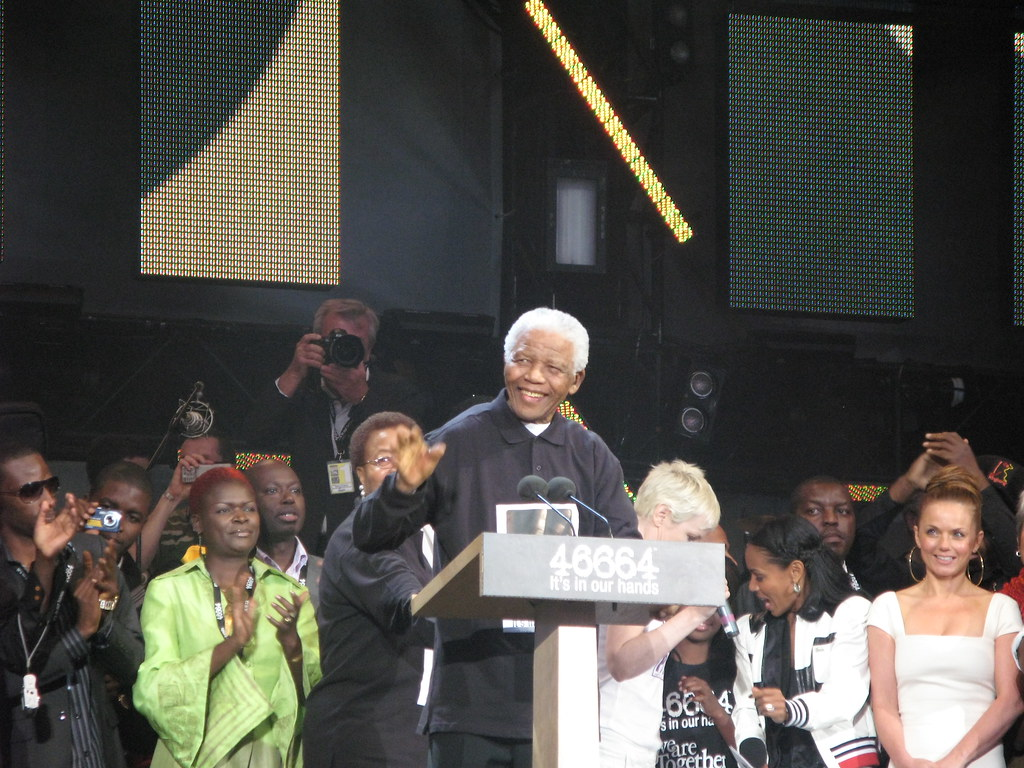 Nelson Mandela speaks to a group of people from a podium, with a smile that seems to reflect his heart for servant leadership