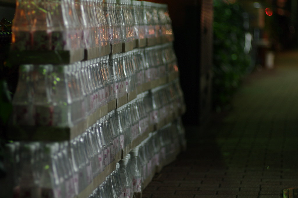 秀栄社の少し手前にあるアラビア食材店(?)前 並ぶ水ボトル