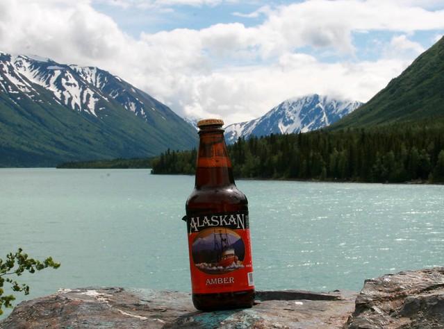 Slightly tilted bottle of Alaskan Amber in front of Kenai Lake