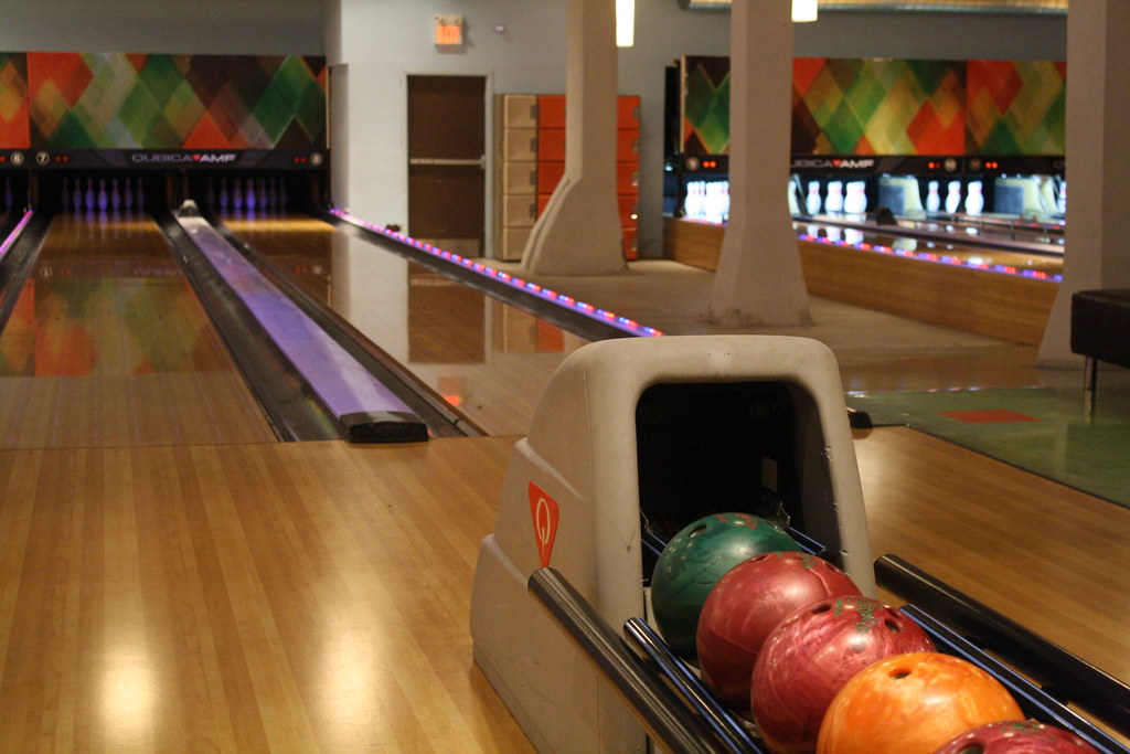 A Picture of a couple bowling lanes and a ball return with multiple balls.
