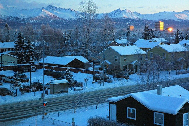 The Golden Glint of Sunset, A regular neighbourhood in old downtown Anchorage -- probably built around the second world war with Saltbox style houses, houses, buildings, mountains, trees, snow, Christmas Eve, Anchorage Alaska USA
