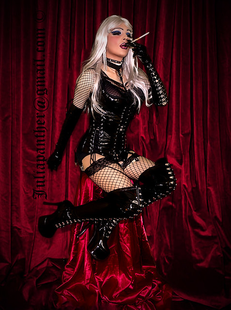 Sensual smoking in sexy latex corset, gloves, boots and fishnet