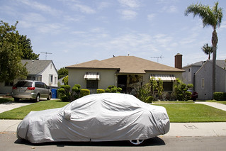 covered car in suburbia | by susan catherine