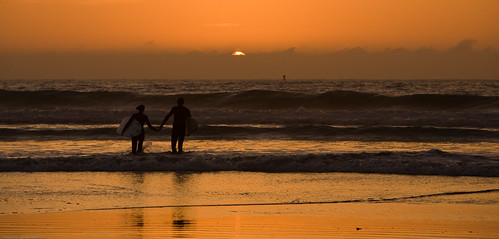 1 of 2 Two surfers in wetsuits, holding hands, walk into the Pacific Ocean   by mikebaird