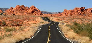 Blacktop winding through red rocks near Valley of Fire State Park in Nevada | by Alaskan Dude