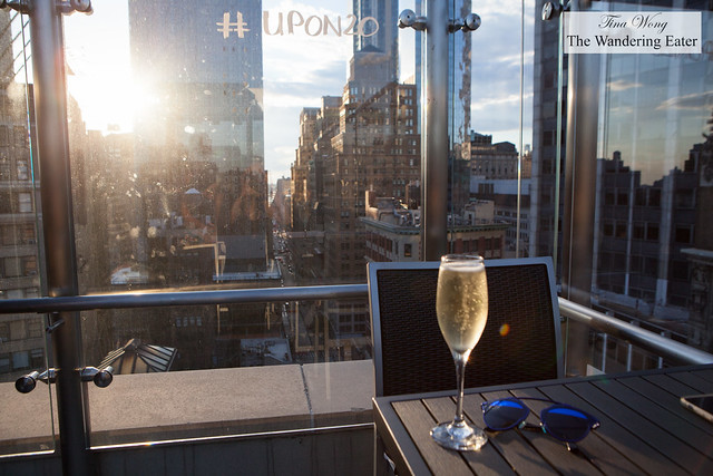 Glass of Prosecco and the view of the sunset and west Manhattan