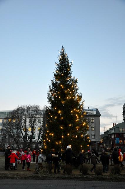 Children singing around a Christmas tree