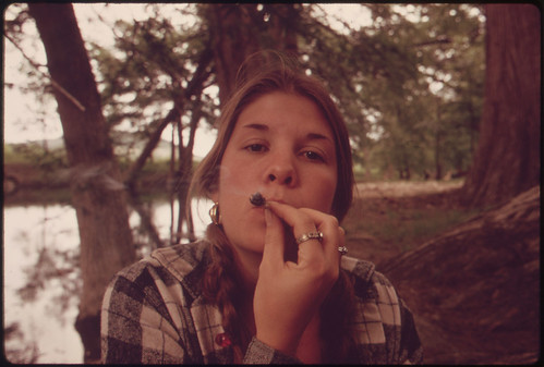 Teenage Girl Smoking Pot in Cedar Woods While on an Outing with Friends near Leakey, Texas. | by The U.S. National Archives