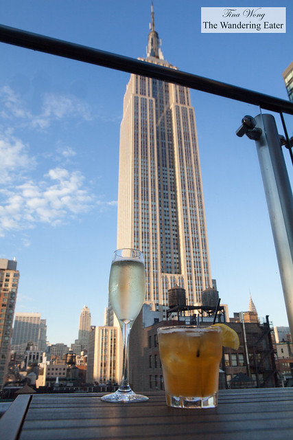Glass of Prosecco and Sunny Honey cocktail with a view of the Empire State Building