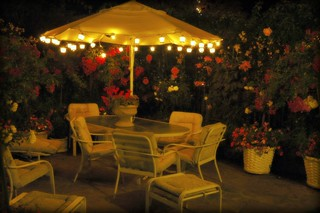 Lit Umbrella, white patio table and chairs, flowering plants in white woven buckets, pink, purple, white roses, and an urn of red flowers, Mill Rose Inn, Half Moon Bay, Night Light Garden, California, USA | by Wonderlane