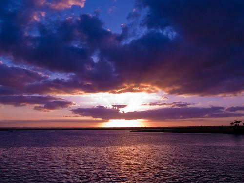 ocean sunset orange clouds bay purple shoreline peach sunrays