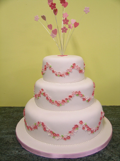 Pink and white wedding cake with hearts and flowers starbursts