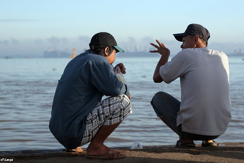 Two Vietnamese men, seen from behind, wearing billed caps and squatting as they have a conversation. The man on the right is gesticulating with his left hand