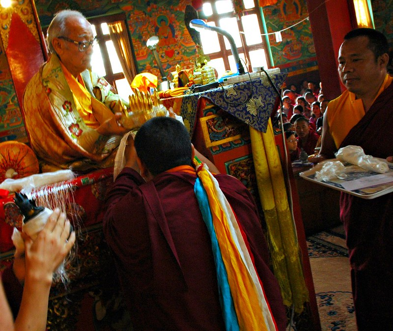 Mandala Offering of the Universe to His Holiness Jigdal Dagchen Sakya on behalf of all who live, five colored scarves like a rainbow, lamas wait with offering khatags and the ku or statue symbolizing the body of the Buddha, Tharlam Gompa, Kathmandu, Nepal