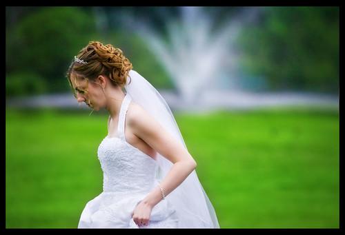 the bride, walking across a field of wet grass | by mitwalter