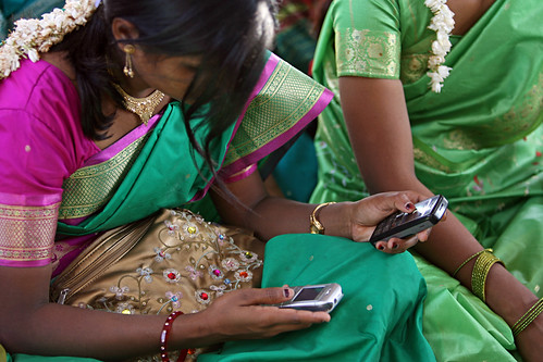 Young women look at their cellphone during a community meeting | by World Bank Photo Collection