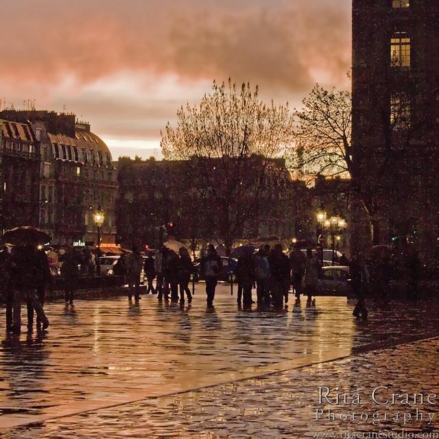 Rita Crane Photography: Parvis de Notre Dame at Sunset / France / Paris / people / rain / reflection / umbrellas / street / building / silhouette / notre dame / sunset  colors