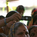 Woman takes photo with cellphone at a community meeting