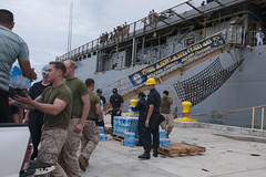 Sailors and Marines load cases of water onto USS Ashland (LSD 48) in preparation to transit to Saipan and support relief efforts there in the aftermath of Typhoon Soudelor. (U.S. Navy/Leah Eclavea)