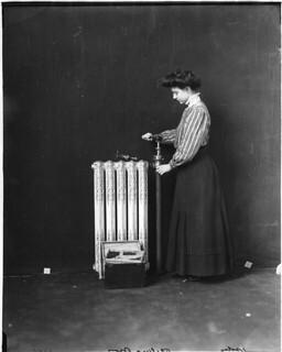 Woman repairing hot water radiator, 1909
