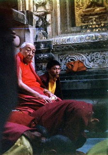 His Holiness Dilgo Khyentse Rinpoche at the Mahabodhi Stupa, watching people prostrate, near the Bodhi Tree, sculptural decoration and gold on a statue, Bodhgaya, India, 1990, photo by Gary