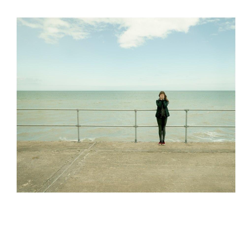girl, railings sea and sky.