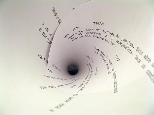 Photo of a page from a play script, furled so the words form a spiral.