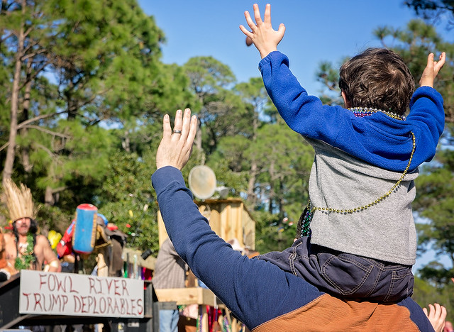 Mardi Gras fans wave at float in the People's Parade during Mardi Gras in Dauphin Island, Alabama