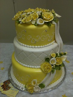 Yellow and white Wedding cake. Fondant with quilted pattern and decorated with gumpaste roses and calla lillies. All dominican cake. Fillings included guava, pineapple and dulce de leche. Frosted in vanilla almond buttercream!!! Yellow is definetly my col | by funcakeandmore