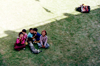 Tibetan kids playing with a dog, on the grass, Sakya College, Rajapur, Uttar Pradesh, India, in 1993