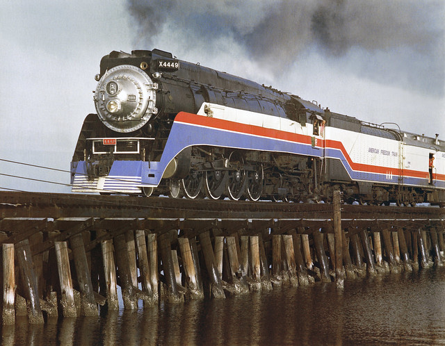 Southern Pacific Daylight GS-4 class 4-8-4 Northern steam locomotive# 4449, painted in AFT colors, leads the American Fredom Train over a railroad trestle as it enters Bradenton, Florida, December 1976