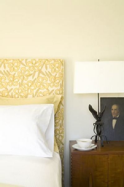 Calm, understated white bedroom + covered headboard