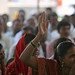A woman raises her hand to speak at a community meeting in Aurangabad