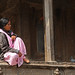 Woman sits on a ledge at a temple in Kathmandu