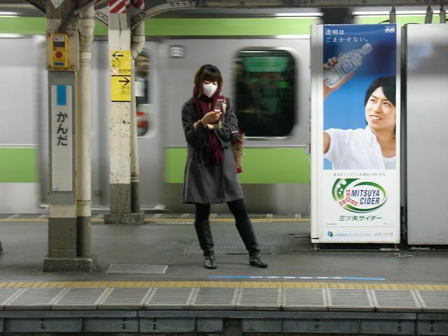masked woman checks her keitai