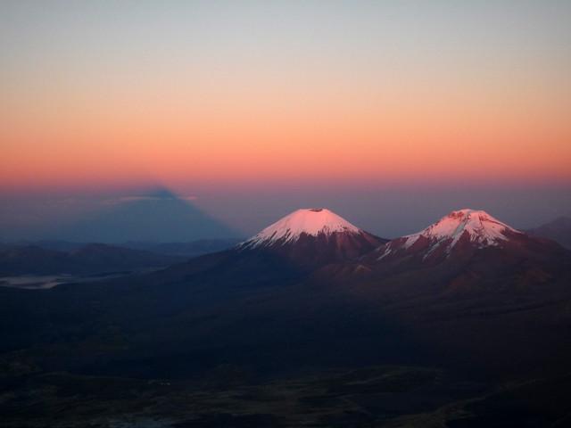 Shadow of Sajama at Sunrise with Parinacota and Pomerape