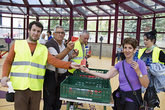 Los/as voluntarios distribuyen el agua y la fruta a participantes