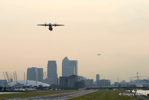 Regional aeroplane is taking off while another is approaching the runway at London City Airport, England, UK.