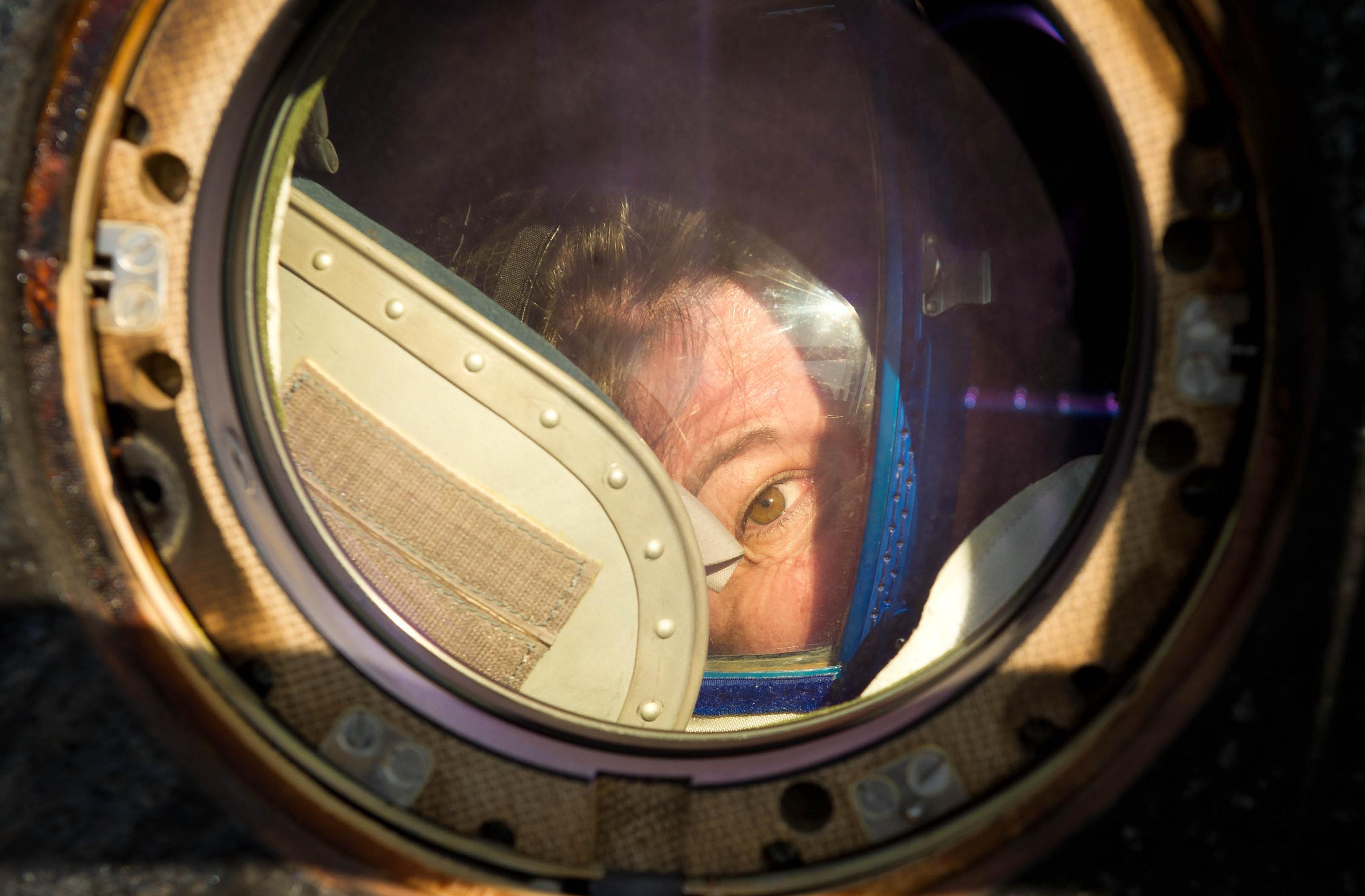 un astronauta guarda fuori dal finestrino della Soyuz appena atterrata