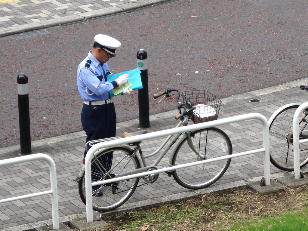 policier devant un vélo qui remplit une contravention