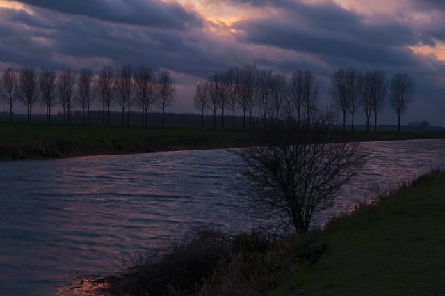 Hertogswetering winterse en stormachtige namiddag met zonsondergang en silhouetten van bomen.1