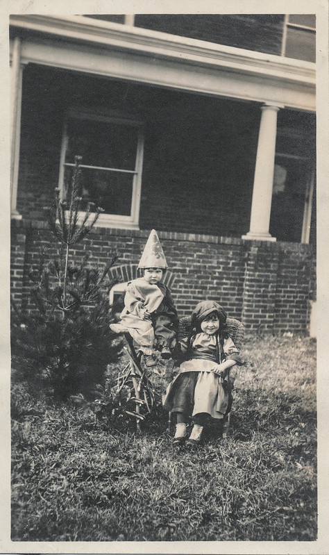 Two children in costumes sitting outside